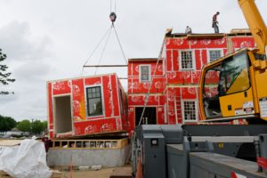 A pre-fab home under construction as a boom-truck lowers a section into position. Courtesy photos